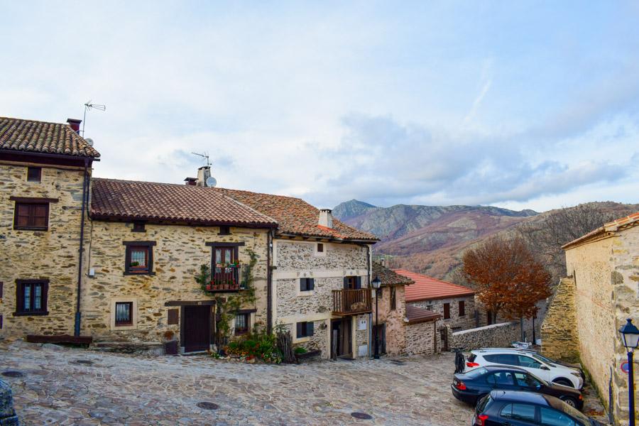 Platz mit typischen Häusern und Blick in die Berge